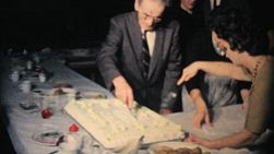 Office management careful cuts a big slab cake at the year end company Christmas party in 1962.