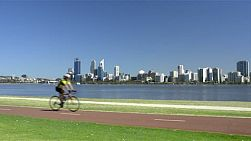 Cyclists riding along a bike path on the south perth foreshore, along the edge of the swan river, with perth city and the river in the background. (western australia)