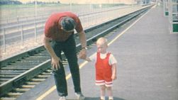 A father and his cute blond haired son waiting for the train to come so they can board in 1967.