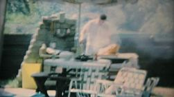 A dad barbeques some delicious food for a group of teenagers enjoying a pool party in 1969.