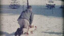 A Dad enjoys riding toboggans down the hill on a beautiful winter's day with his kids in December 1967.
