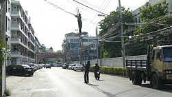 Two Asian hydro linemen working dangerously in the middle of the street in the suburbs of Bangkok, Thailand.