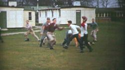 A group of college aged friends play a fun game of pick up football outside of their dorm in the fall of 1950.