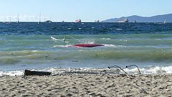A capsized shipwrecked sailboat washes up on the beach of English Bay in Vancouver, BC, Canada.