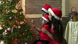 A beautiful Asian family enjoy decorating the Christmas tree together.