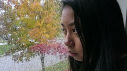 A sad depressed 13 year old Asian teenage girl sits by a window watching the rain fall.