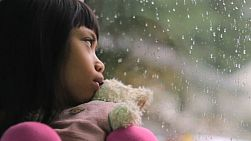 A depressed little seven year old Asian girl sits by a rainy window with her Teddy Bear.