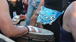 A djembe drummer lays down a funky beat while a female belly dancer dances in the Drum Circle at Venice Beach, California.
