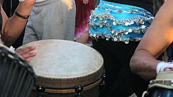 A close up shot of a djembe drummer lays down a funky beat while a female belly dancer dances in the Drum Circle at Venice Beach, California.