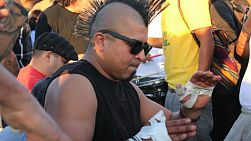 A djembe drummer with a large Mohawk lays down a funky beat at the Drum Circle at Venice Beach, California.