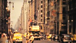 A shot of busy downtown New York at Fifth Avenue including a tour bus passing by in 1940.
