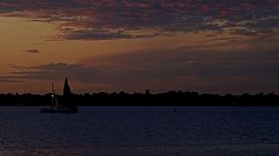 Yachts sailing on Perth's Swan River as the last light of the day fades on the horizon.