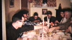 An extended family sits down to enjoy a wonderful home-made turkey Christmas dinner together.