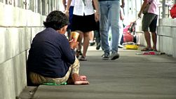 An elderly Asian woman receives money from people passing by as she begs on the streets of Bangkok, Thailand.