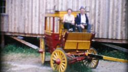 An cute elderly couple pretend to ride an old stage coach and enjoy exploring an historic old village in 1967.