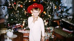 An excited little boy gets a red cowboy hat and gun for Christmas in Cleveland, Ohio in 1956.