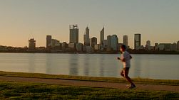 Various people passing by as they run and walk along the South Perth Foreshore, with a view of the Swan River and city skyline in the background.