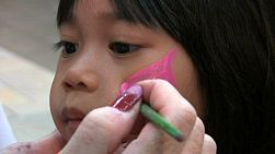 A cute little Asian girl sits patiently while the artist paints a pink butterfly on her face.