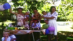 Party guests enjoying a combined 1st birthday party in Australia, in 1983, with the mothers and toddlers celebrating their birthdays standing up front to celebrate together.  Film has been transferred using a frame-by-frame scan to produce the highest quality.