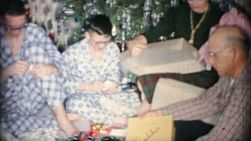 A family enjoys spending time together, opening gifts and celebrating Christmas in Akron, Ohio in 1963.