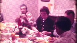 A beautiful Christmas tree stands proud while a family enjoys a delicious holiday meal together in 1972.