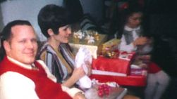 A family enjoys opening Christmas presents together on Christmas morning in 1970.