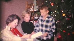 A family enjoys opening Christmas presents together on Christmas morning in 1962.