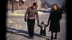 A young family takes a stroll down a snowy street with their little girl in the middle of a cold winter in the prairies.