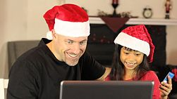 A father and daughter enjoy spending time together and doing some online Christmas shopping using their laptop and credit card.
