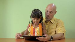 A father and his Asian daughter enjoying using a tablet computer together, ending in a happy smile, kiss and hug.
