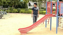 An Asian father and son playing together on a slide in a public park.