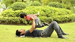 An Asian father and son playing together on the grass in a park.