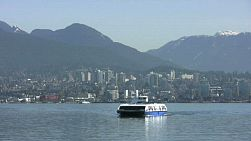 A ferry approaches the pier against a gorgeous city and mountain backdrop. (HD 1080p30)