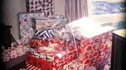 A festive Christmas scene with a boy's new train set, presents and gifts and his Cat during Christmas in 1962.