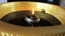 A flame flickers in a bowl of oil at a Buddhist temple in Bangkok, Thailand.