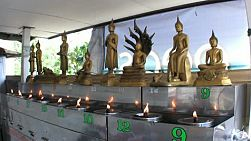 Oil burners with flames burn in front of a collection of gold plated Buddha statues on the temple grounds in Bangkok, Thailand.