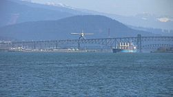 A float plane flies over bridge and lands in a pretty harbor. (HD 1080p30)
