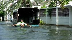 A Thai man floats down a flooded Bangkok street in an inner tube during the floods of 2011.
