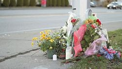Flowers at a busy intersection mark a tragic unnecessary death.