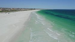 Drone shot flying low over Mullaloo Beach in Perth, Western Australia on a clear windy day.
