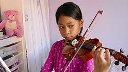 A cute little 9 year-old Asian girl diligently practices her violin in her bedroom.
