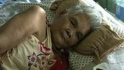 A sick older Thai lady lays in bed and battled the heat while she lives in the slums of Bangkok, Thailand.