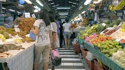 A fresh fruit market in Bangkok, Thailand, with shoppers and a large variety of fruit for sale.