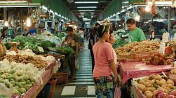 Customers buying fresh fruit and vegetables at a fresh food market in Bangkok, Thailand.