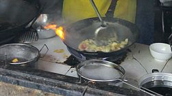 A cook makes a delicious Thai egg omelet in a wok in northern Thailand.