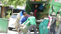 A group of male trash collectors pick up garbage on the streets of Bangkok, Thailand.