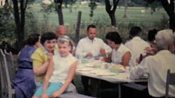 A girl and her mother enjoy a big summer picnic get together reunion in 1962.
