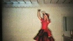 A pretty teenage girl in a red dress performs her dance routine complete with castanettes at her recital.