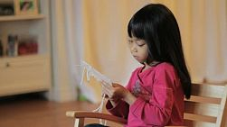 A cute little 5 year old Asian girl enjoys doing some stitching in her rocking chair.