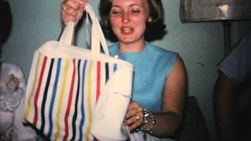 An excited female young adult enjoys opening gifts and presents at her bridal shower in 1967.